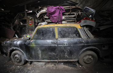 De-registered Premier Padmini taxi is pictured covered in dust with love hearts etched on its windows inside a scrapyard in Mumbai