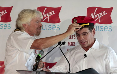 Richard Branson (L)  places a sailor's hat on Virgin Cruises' President and CEO Tom McAlpin during a news conference at the Perez Art Museum in Miami