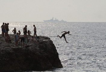 A man jumps into the waters of the Black Sea, with a Russian warship seen in the background, in Sevastopol