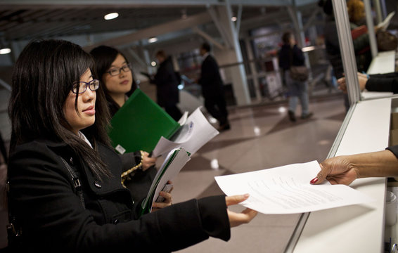 A student hands a copy of her resume to an official before entering a job fair in New York