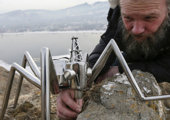 """Russian artist Slonov sets up props he called """"Oil Mosquitoes"""", for a demonstration of an installation on a bank of the Yenisei River in Krasnoyarsk"""