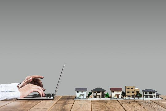 住宅模型,ノートパソコンを操作する人の手