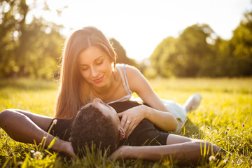 Nature romance - mixed race couple lying in grass