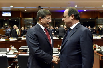 Turkish PM Davutoglu shakes hands with French President Hollande during an EU-Turkey summit in Brussels