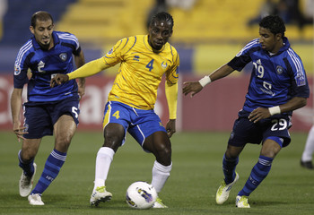 Abdullatif al-Ghannam of Saudi Arabia's Al-Hilal and teammate Mohammed Salem fight for the ball with Lawrence Quaye of Qatar's Al-Gharafa during their AFC Champions League soccer match in Doha
