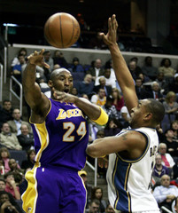 Bryant of the Los Angeles Lakers passes the ball off to a teammate as Butler of the Washington Wizards defends on the play during the second half of their NBA basketball game in Washington