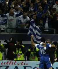Greece's head coach Santos celebrates with Karagounis after defeating Romania during their 2014 World Cup qualifying soccer match in Bucharest
