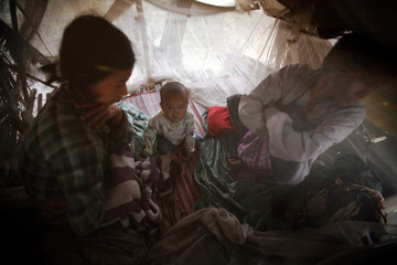 A family wakes up in the early morning behind a mosquito net in their tree-house built for protection from wild elephants in Kyar Chaung village, Taikkyi Township