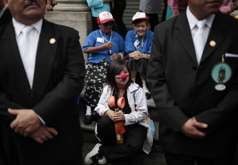 A girl dressed as a clown looks at the procession of the Virgen de la Asuncion in central Guatemala City