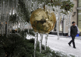 Icicles hang down from a Christmas tree, with an Interior Ministry officer passing by in the background, in central Moscow