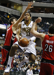 Pacers' Granger puts up a shot after getting between Raptors' Turkoglu and Bargnani during the third quarter of their NBA basketball game in Indianapolis
