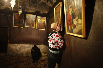 A worshipper kisses a picture hanging inside the Grotto, in the Church of the Nativity in Bethlehem