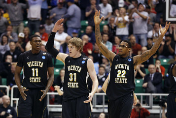 Wichita State players Cleanthony Early (11), Ron Baker (31) and Carl Hall (22)  celebrate during the second half of their third round NCAA tournament basketball game against Gonzaga in Salt Lake City, Utah