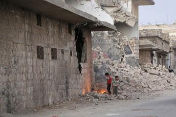 Children light a fire near damaged buildings in Maarat Al-Nouman, south of Idlib province