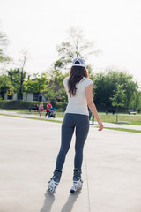 Pretty young woman in the park in roller skates