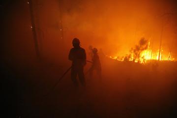 Firefighters attempt to extinguish a fire burning in Povoa de Calde, near Viseu