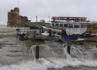 Fisherman attempt to anchor their boats amidst a storm and strong winds at the harbour of the ancient city of Byblos, in northern Beirut
