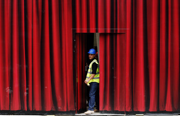 A worker closes a door in a hoarding made to look like a theatre curtain, at a construction site in Covent Garden in London
