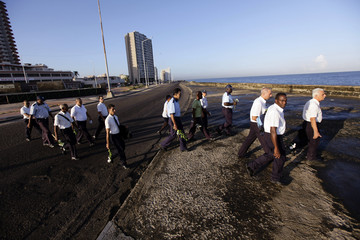 """Cuban state workers walk to throw flowers in the sea on Havana's seafront boulevard """"Malecon"""" in honor of rebel revolutionary commander Camilo Cienfuegos"""