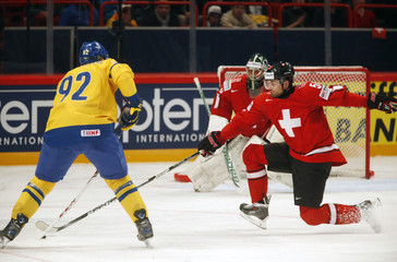 Sweden's Landeskog fights for the puck with Switzerland's Furrer during their 2013 IIHF Ice Hockey World Championship preliminary round match at the Globe Arena in Stockholm