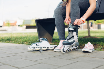 Young woman puts on roller skates while in a park