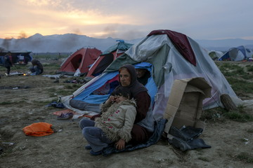 A woman with a child sits in front of their tent at a makeshift camp for migrants and refugees at the Greek-Macedonian border near the village of Idomeni