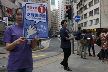 Edward Lau, a businessman who participated in Occupy Central protests and is running for the upcoming district elections, campaigns with a supporter in Hong Kong