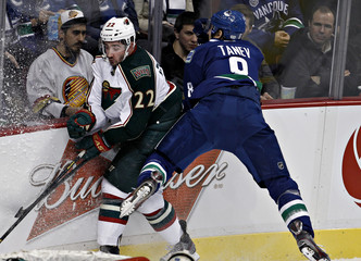 Vancouver Canucks' Tanev crashes into the boards while going after Minnesota Wild's Clutterbuck during their NHL hockey game in Vancouver