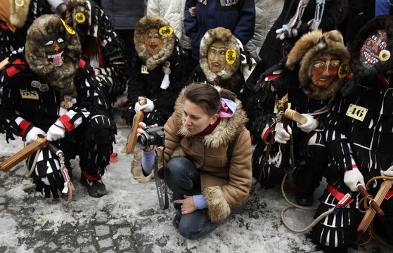 A woman takes pictures surrounded by masked characters during the Lole Parade in the Transylvanian town of Sibiu