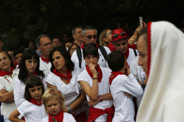 People wait to see the statue of San Fermin, patron saint of the San Fermin festival, being carried through the streets during a procession in his honour in Pamplona