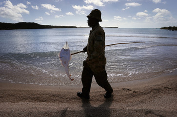 Indigenous soldier from Australia's NORFORCE unit carries a shovelnose guitarfish impaled on a spear after hunting on Astell Island, inside Arnhem Land