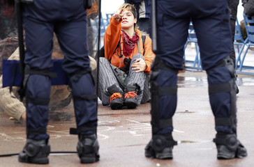 An anti G20 demonstrator sits behind French policemen during a protest against globalisation in Nice