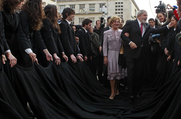 Lula da Silva and his wife Marisa walk over students' coats as they arrive at the Coimbra University