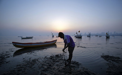 A fisherman anchors his boat in the low tide sand as the sun sets in Mumbai