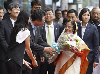Indian President Pratibha Devisingh Patil receives flowers from South Korean officials upon her visit to a memorial site for Indian poet Rabindranath Tagore in Seoul