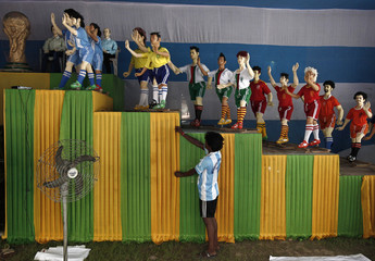 "An Indian soccer fan of Argentina adjusts a cloth in front of clay models of soccer players inside a ""Pandal"" in Kolkata"