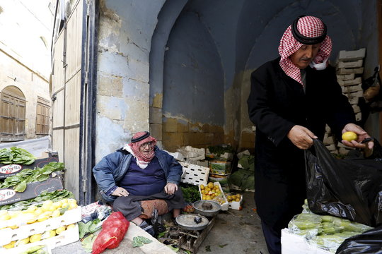 A man buys vegetables from one of the shops at the Hammam Street Market, on one of the oldest commercial streets in Salt, Jordan