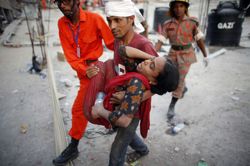 Rescue workers carry a garment worker who was trapped in the Rana Plaza building which collapsed, in Savar