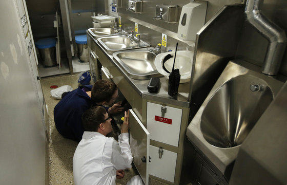 BAE Systems workers install sinks in a crew bathroom onboard HMS Artful one of the Royal Navy's Astute class submarines as it approaches completion at the company's Barrow shipyard