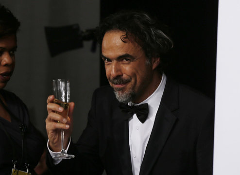 "Director Alejandro Inarritu holds a glass of champagne backstage before posing with his Oscar for best original screenplay for ""Birdman"" at the 87th Academy Awards in Hollywood"