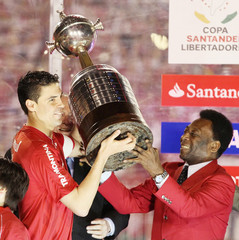 Bolivar of Internacional holds up the trophy with the help of Pele after defeating Guadalajara Chivas in Porto Alegre