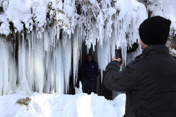 A young man takes a picture of a frozen waterfall at around minus 26 degrees Celsius (minus 14.8 degrees Fahrenheit) in the village of Jezerc