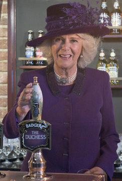 Britain's Camilla, Duchess of Cornwall poses for a photograph behind a beer tap during a visit to 'The Duchess of Cornwall Inn' in Poundbury