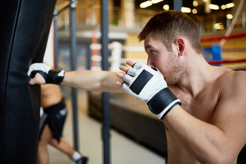 Young sportsman kicking boxing-bag in gym