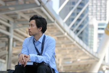 Frustrated stressed young Asian businessman sitting on the walkway and looking on far away in the city background.