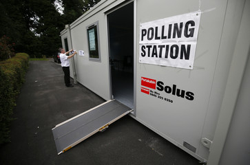 A man puts up a sign at a polling station for the Referendum on the European Union in Heald Green, Stockport, Britain