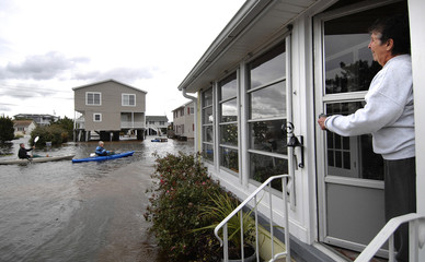 A resident talks to neighbours kayaking down a flooded neighbourhood street from the porch of her house in the aftermath of Hurricane Sandy in South Bethany Beach