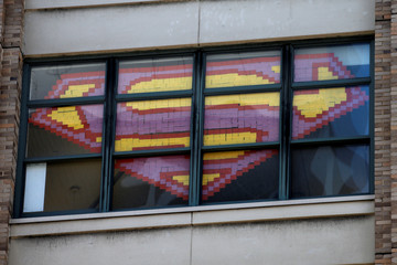 """An image of the Superman Logo created with Post-it notes is seen in windows at 200 Hudson street in lower Manhattan, New York during """"Post-it note art war\"""