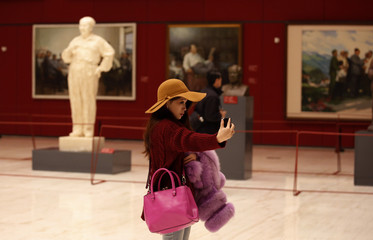 A woman takes a self-portrait with her mobile phone in front of various artworks of China's late Chairman Mao at an art exhibition celebrating the upcoming 120th anniversary of the birthday of the former leader in Beijing