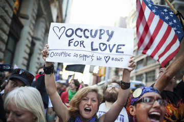 A protester holds up a poster as members of Occupy Wall Street march from Washington Square Park to the Financial District in New York